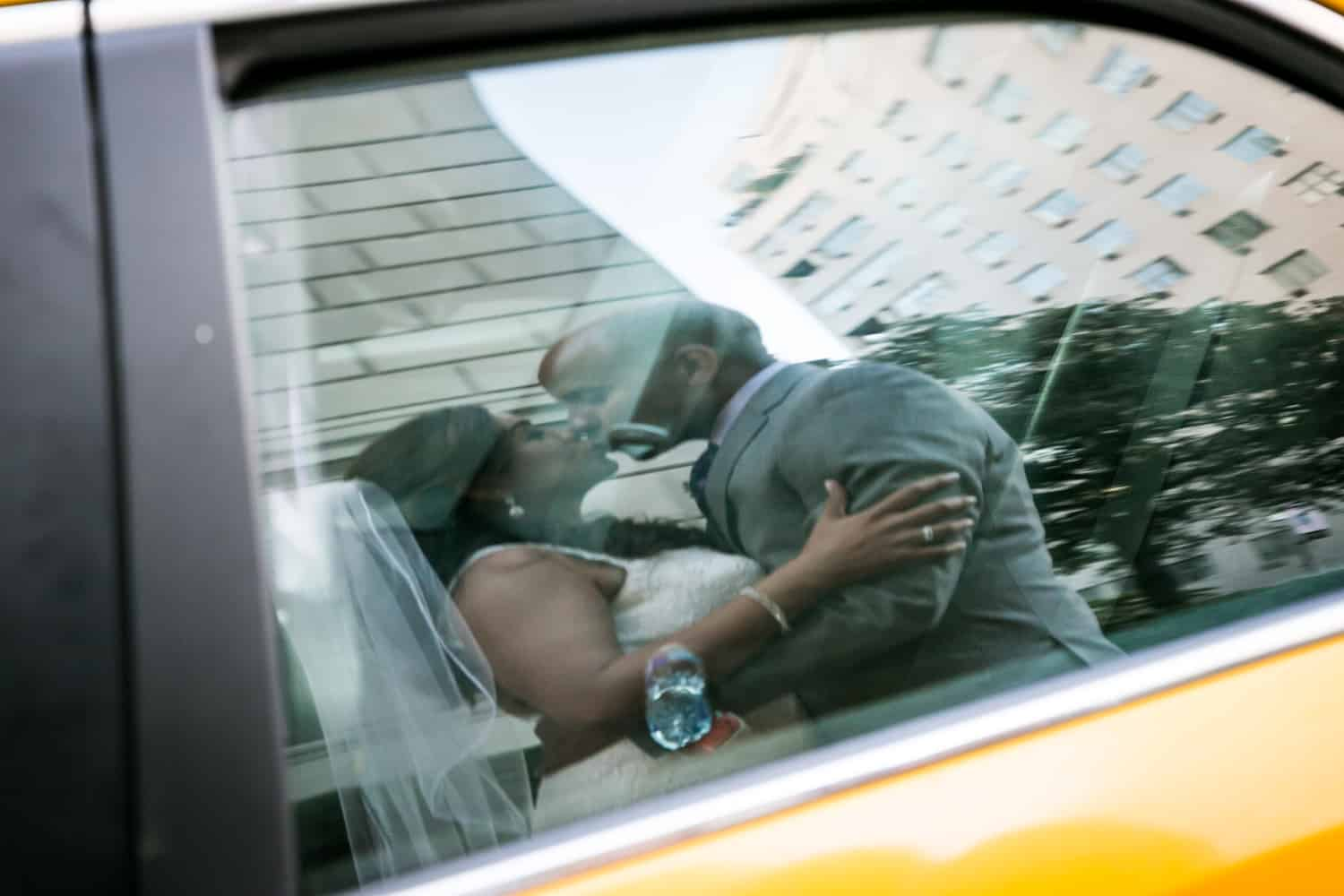 Reflection in taxi cab window of bride and groom kissing