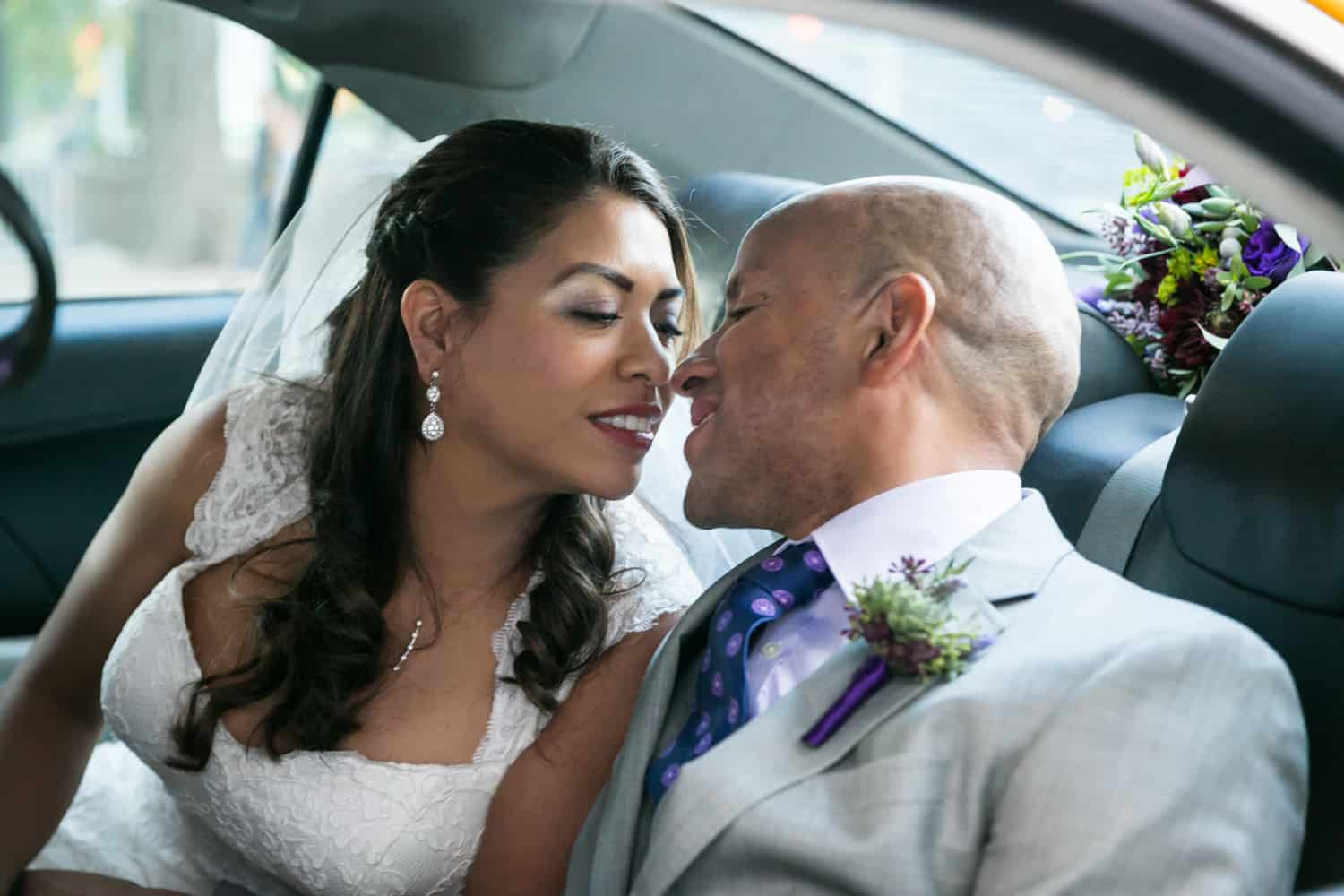 Bride and groom about to kiss in the back of a taxi cab