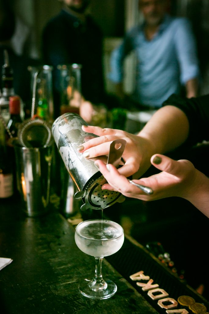Close up of female bartender hand pouring cocktail for an article on how to book hotel room blocks