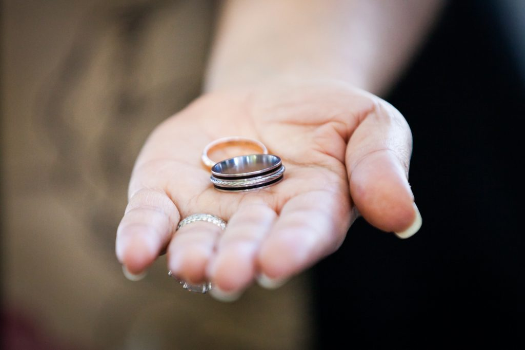 Close up of officiant's hand holding out wedding rings