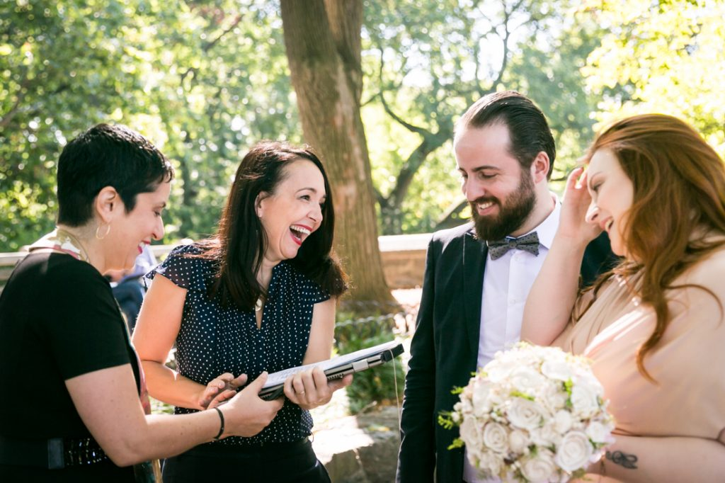 Bride, groom, officiant, and wedding planning laughing together for an article on how to plan a destination wedding