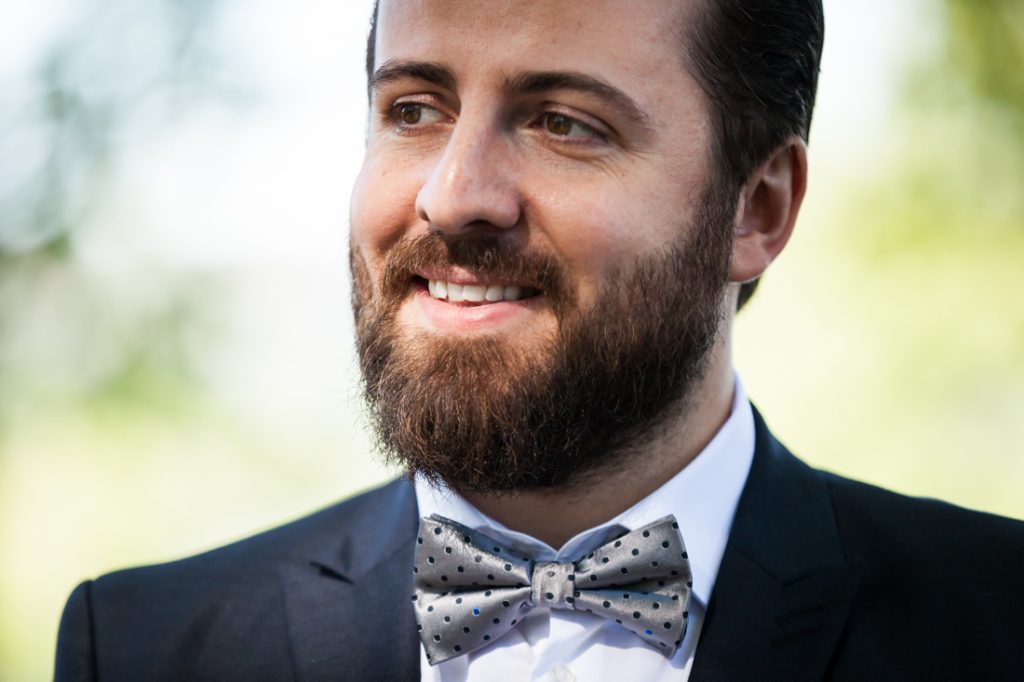Groom wearing grey bow tie and looking to side