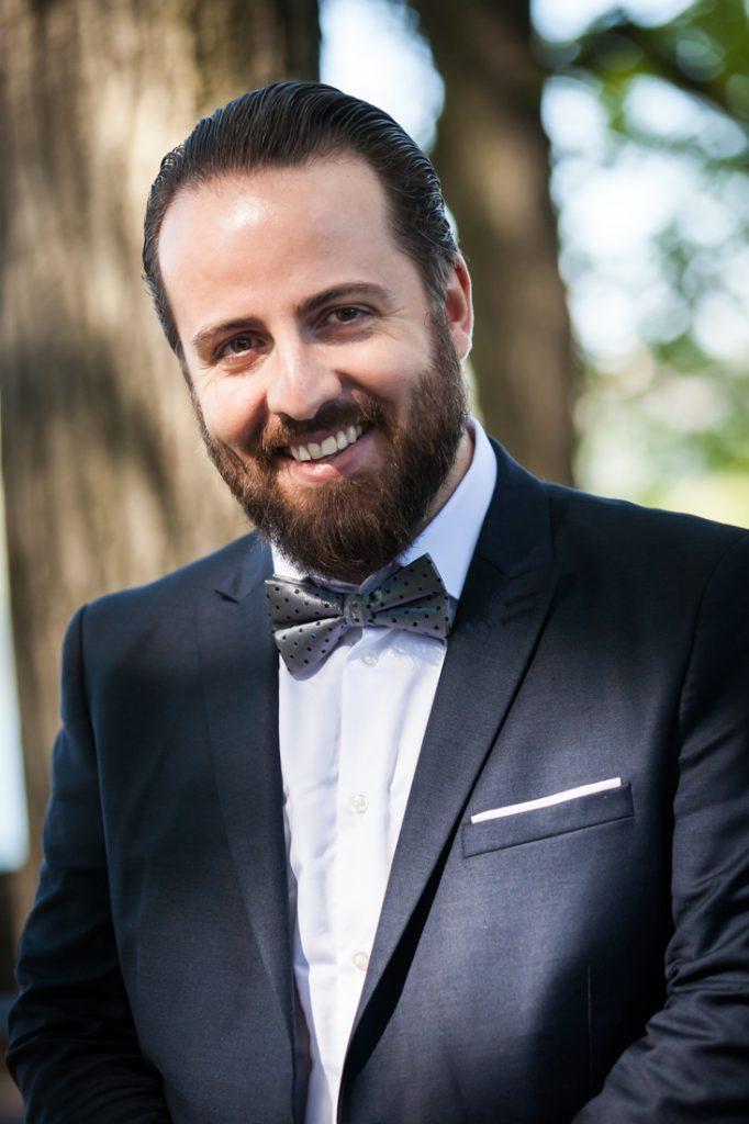 Smiling groom wearing grey bow tie