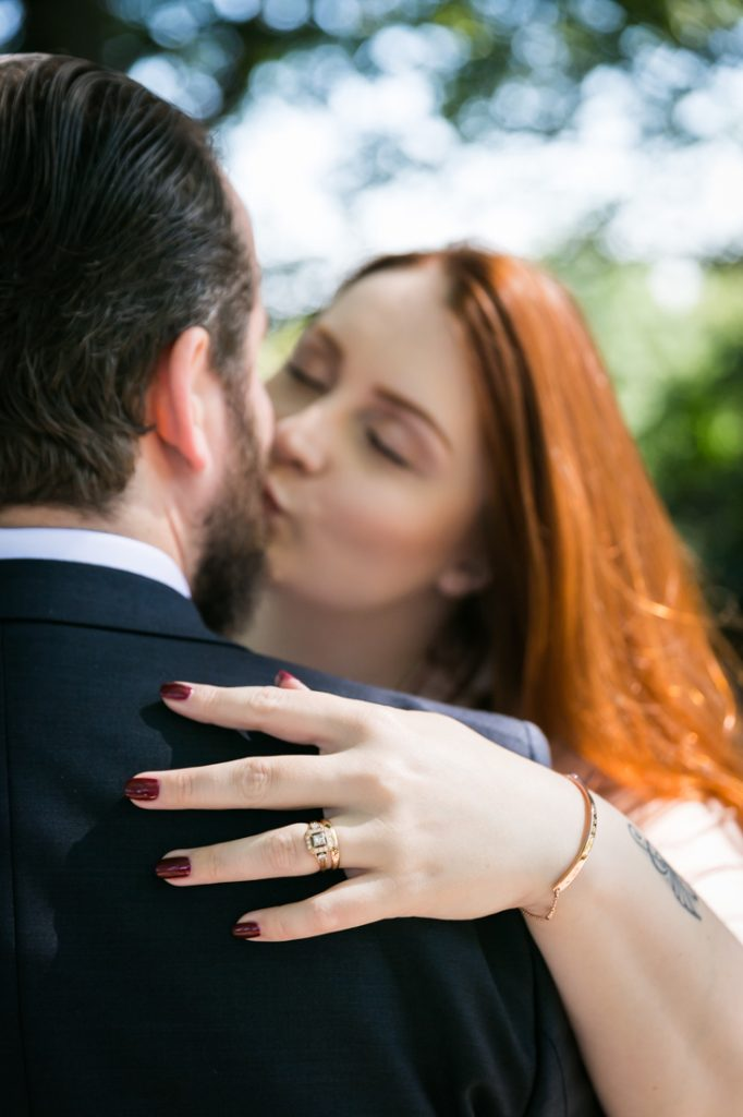Bride and groom kissing with bride's hand on groom's shoulder