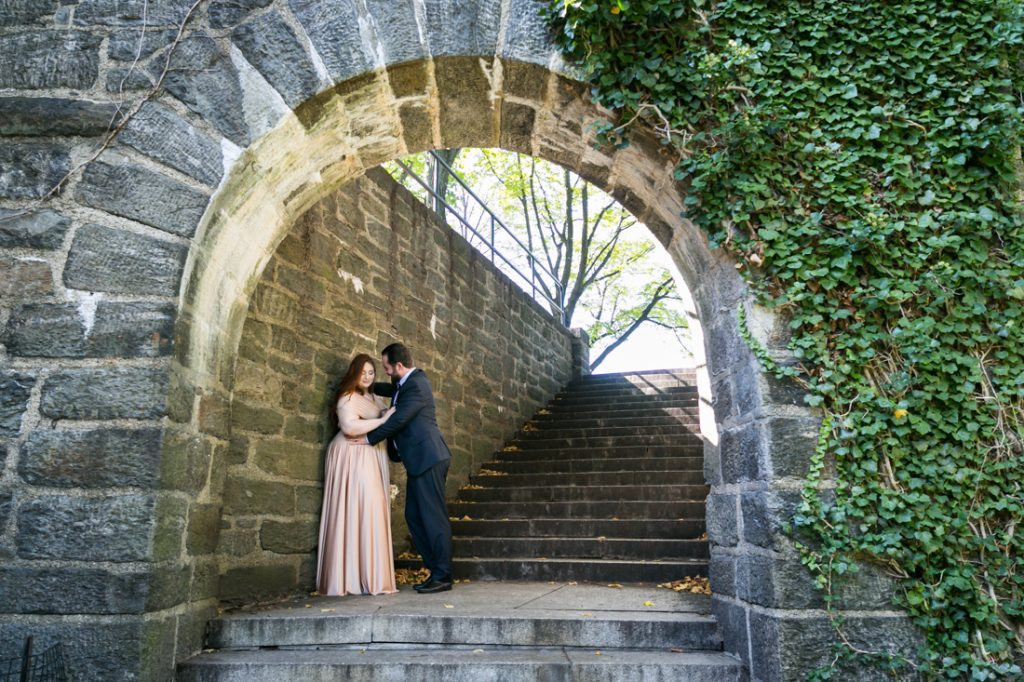 Bride and groom against stone wall in Fort Tryon Park