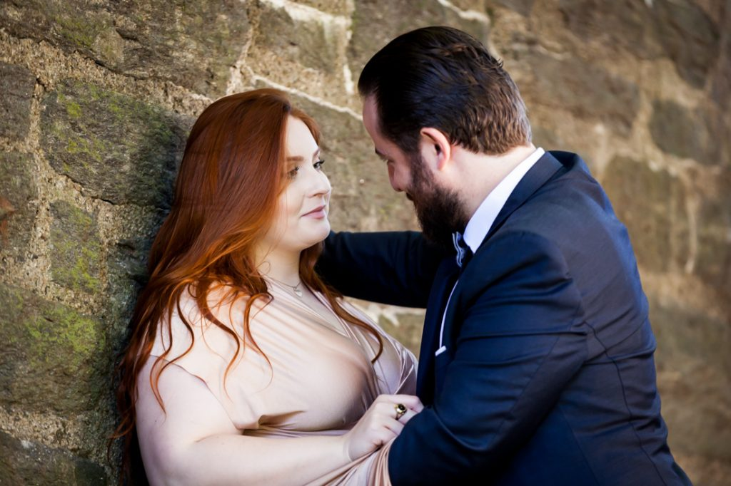 Groom leaning over bride on stone wall in Fort Tryon Park