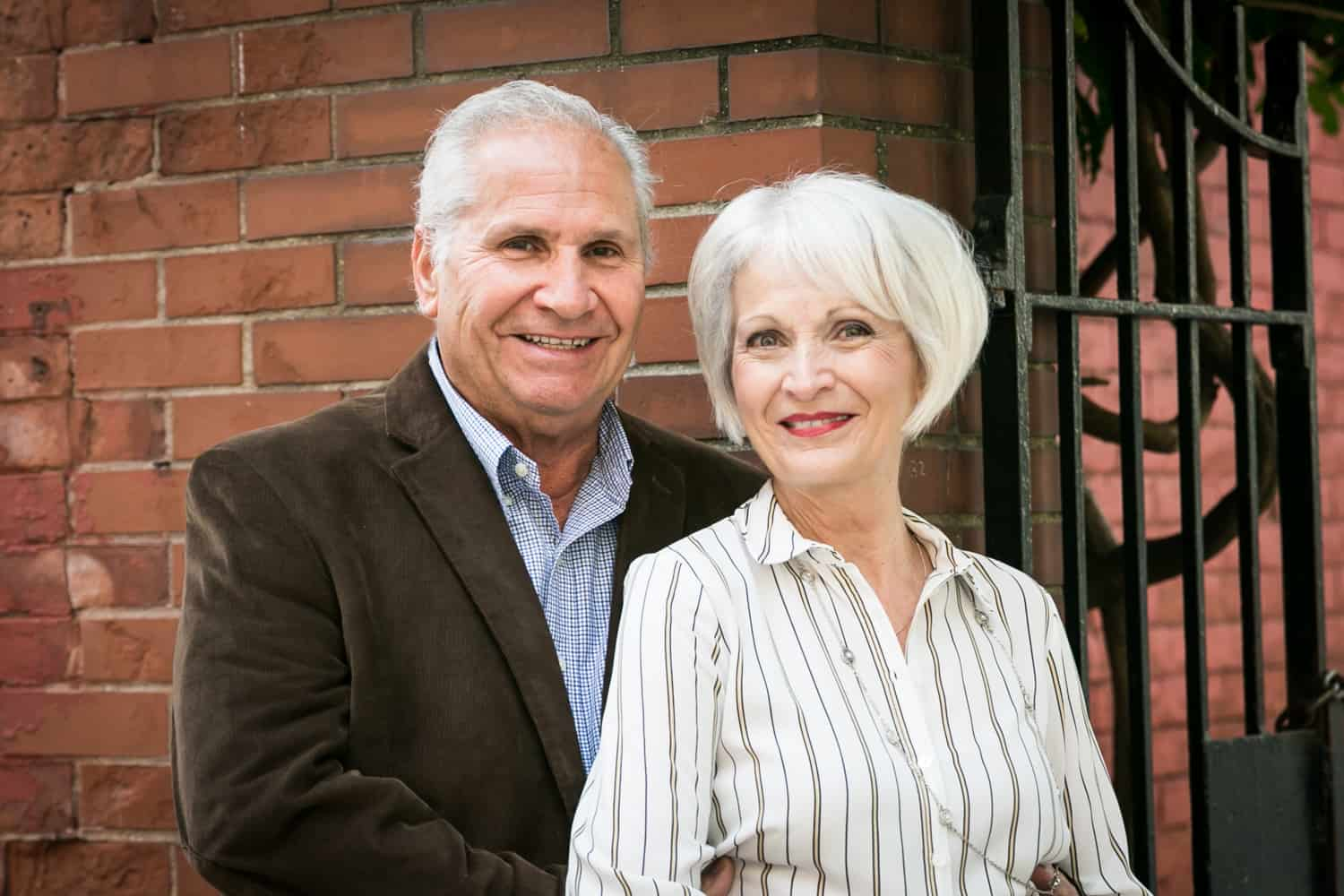 Photojournalistic portraits of older couple with brick wall background