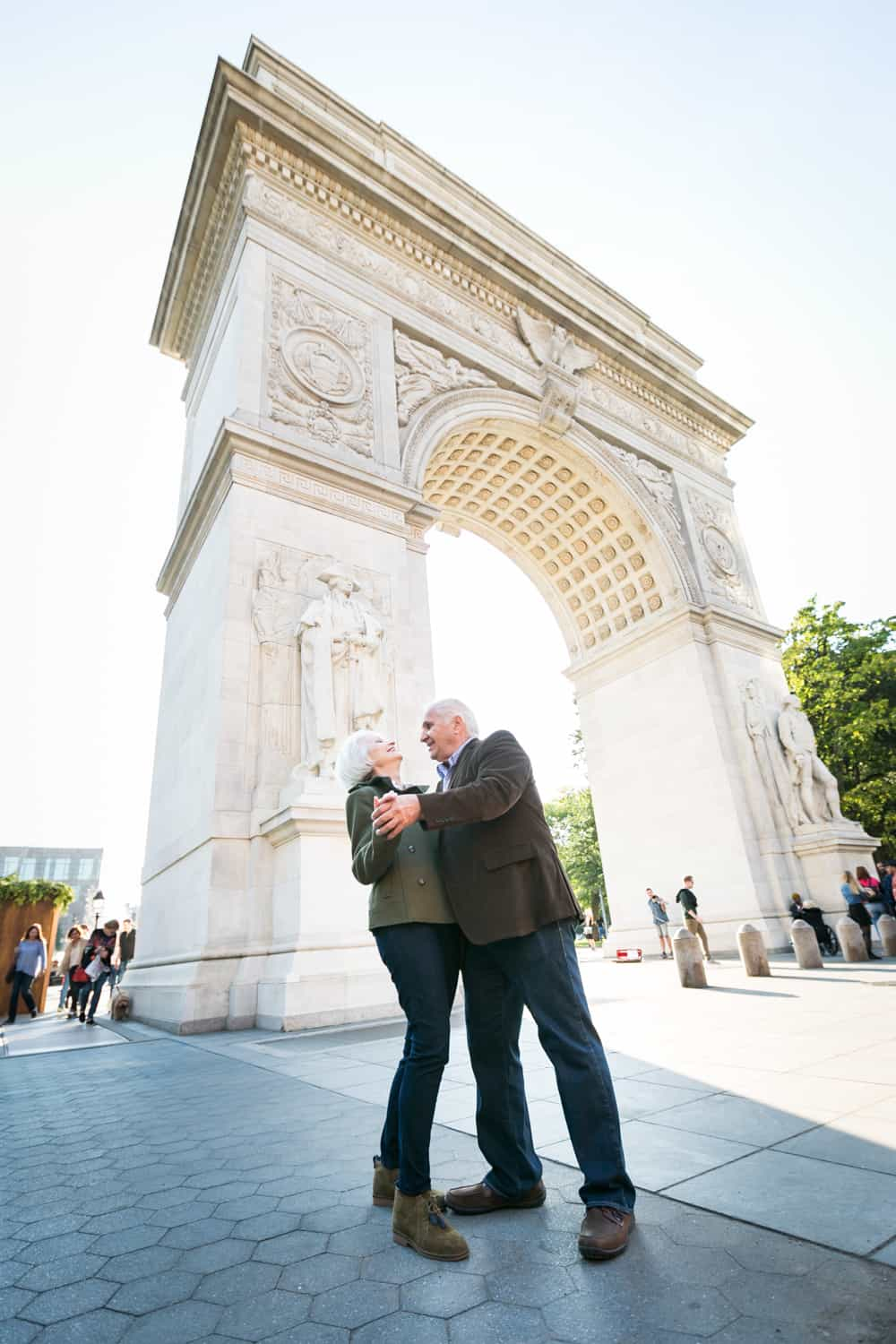 Photojournalistic portraits of older couple dancing in front of Washington Square Park arch