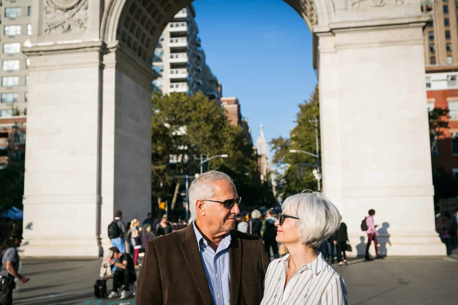 Photojournalistic portraits of older couple wearing sunglasses in front of Washington Square Park arch