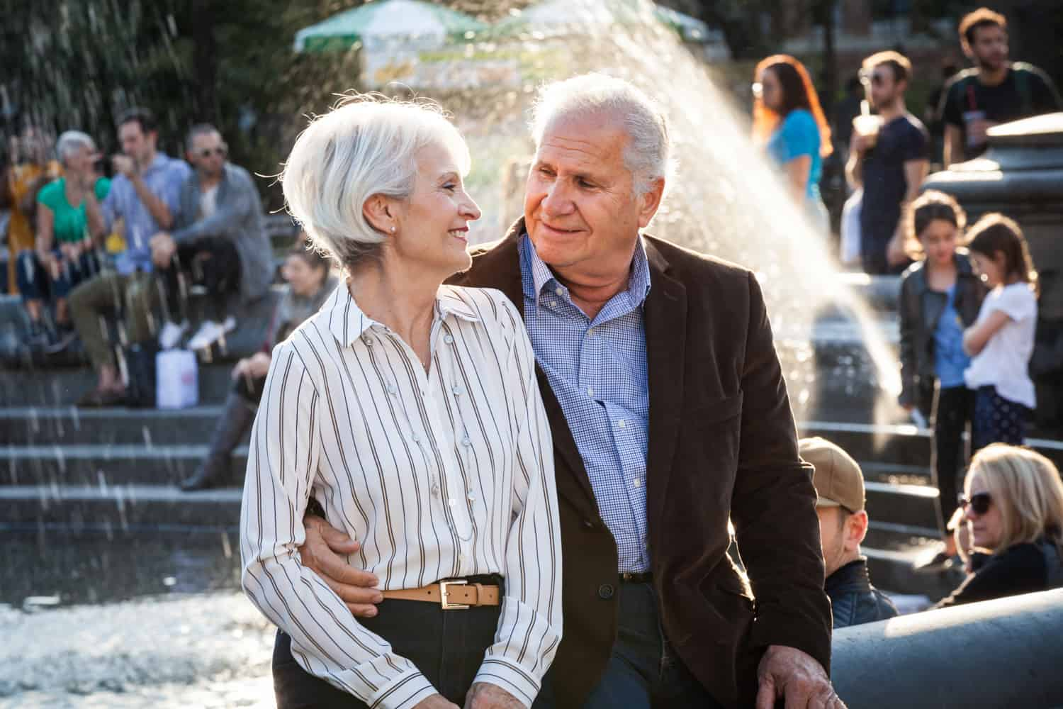 Photojournalistic portraits of older couple sitting on side of fountain in Washington Square Park