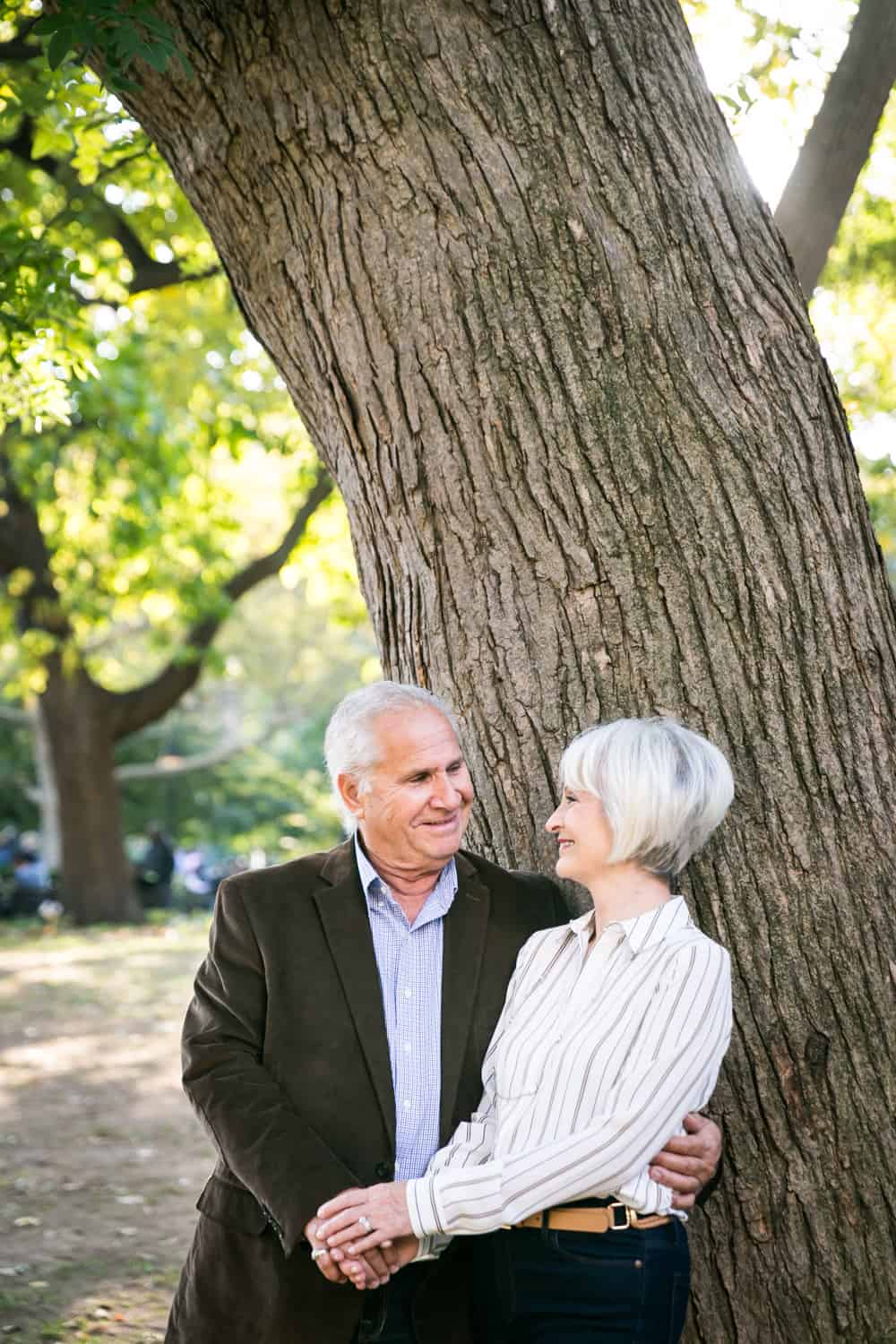 Photojournalistic portraits of older couple standing under tree in Washington Square Park