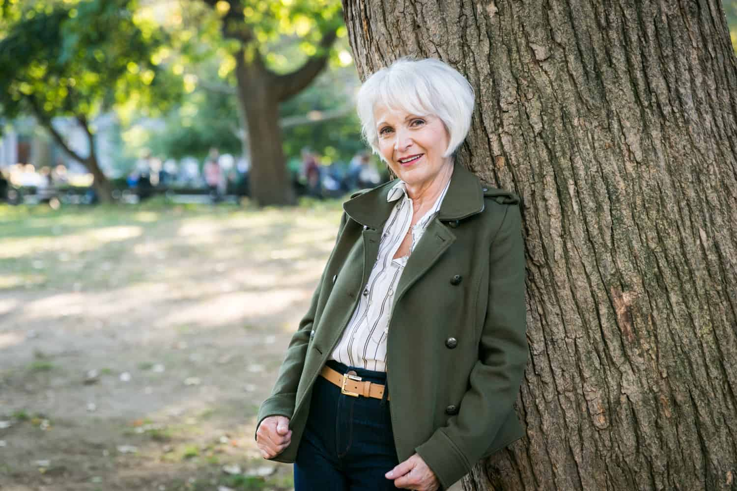 Older woman in olive jacket standing by tree