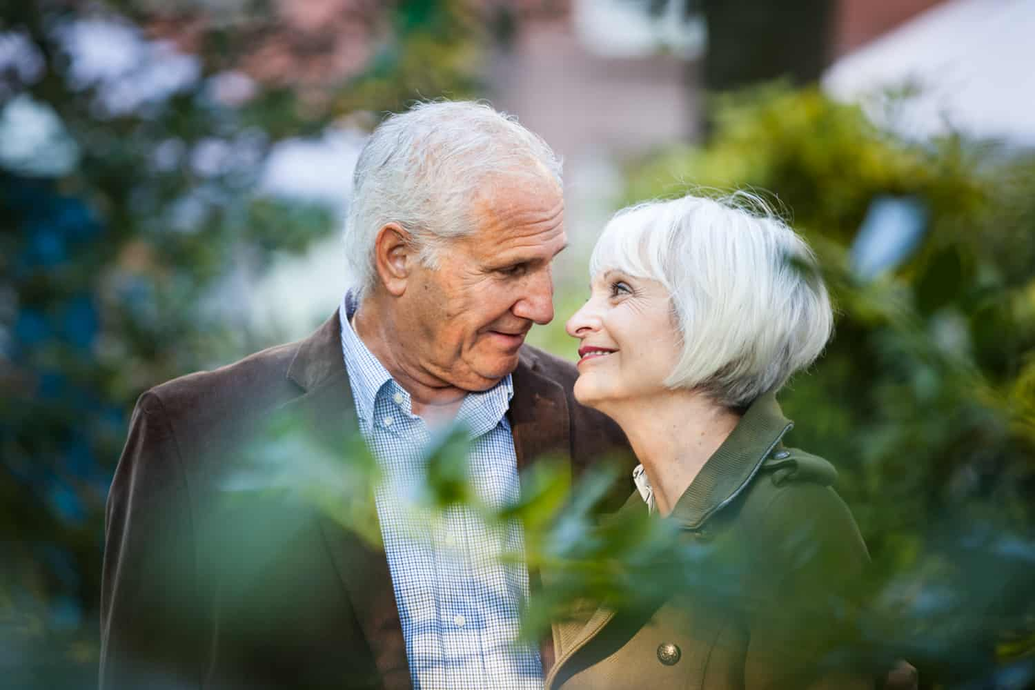 View through branches of older couple looking at one another