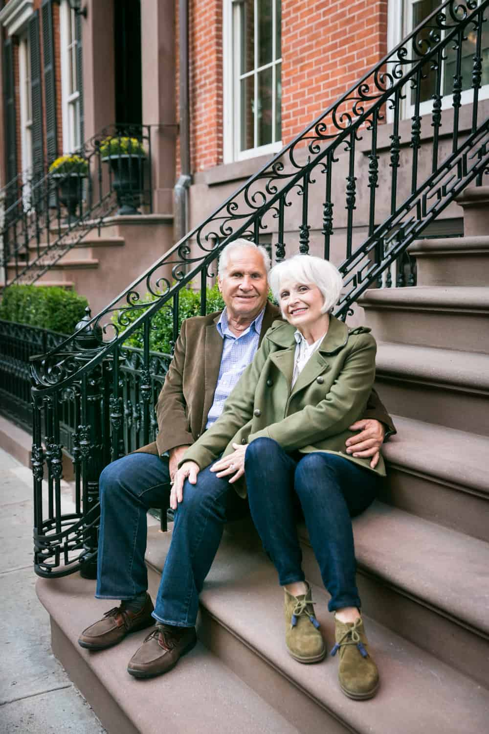 Older couple sitting on brownstone stairs