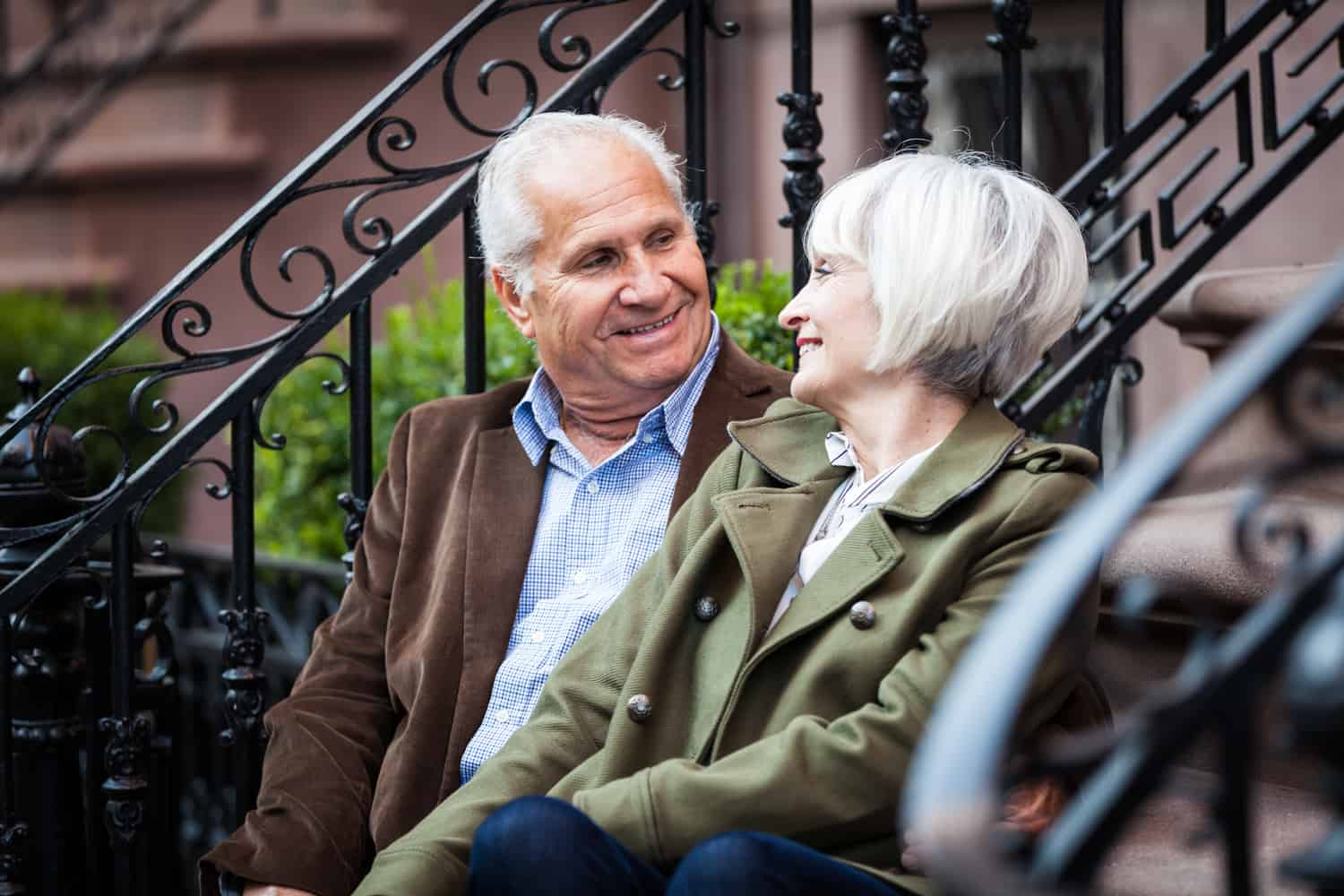 Older couple looking at one another while sitting on brownstone stairs