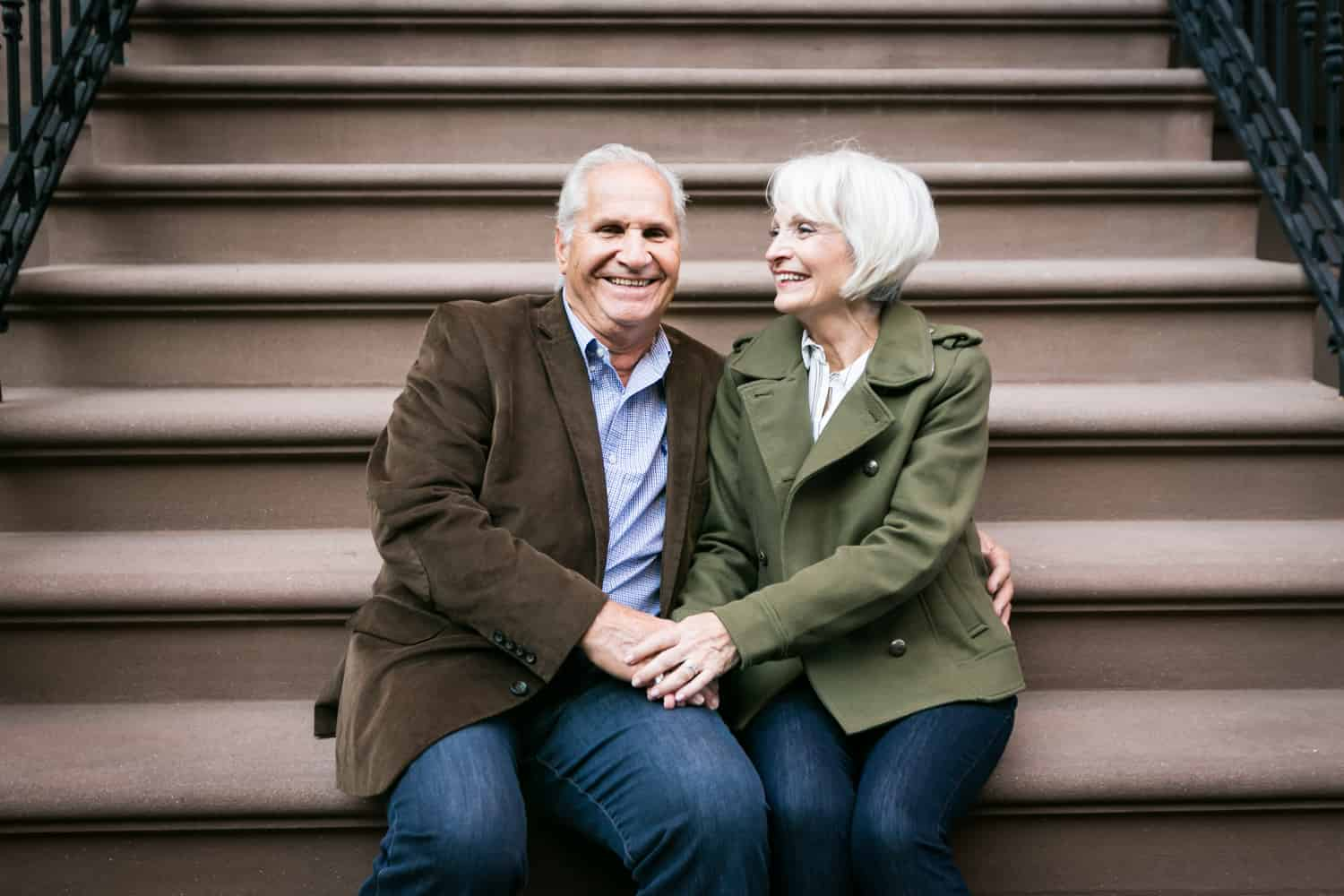 Older couple holding hands while sitting on brownstone stairs