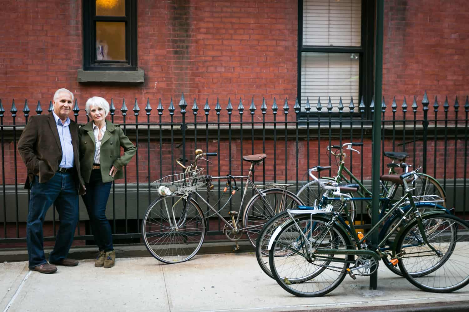 Older couple leaning on fence to left of parked bicycles