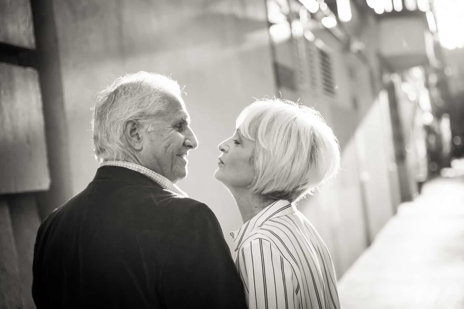 Black and white photo of older couple on sidewalk