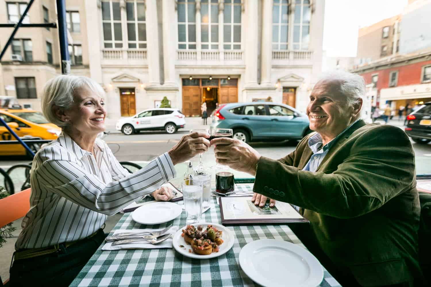 Older couple toasting glasses at sidewalk restaurant