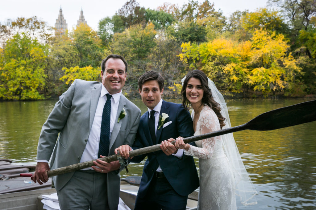 Bride, groom, and groomsman in a Central Park rowboat