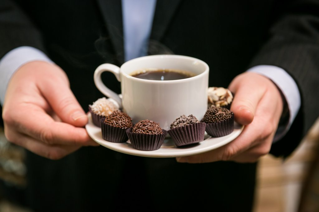 Hands holding a cup of coffee with chocolates around the plate for article on creative guest favors