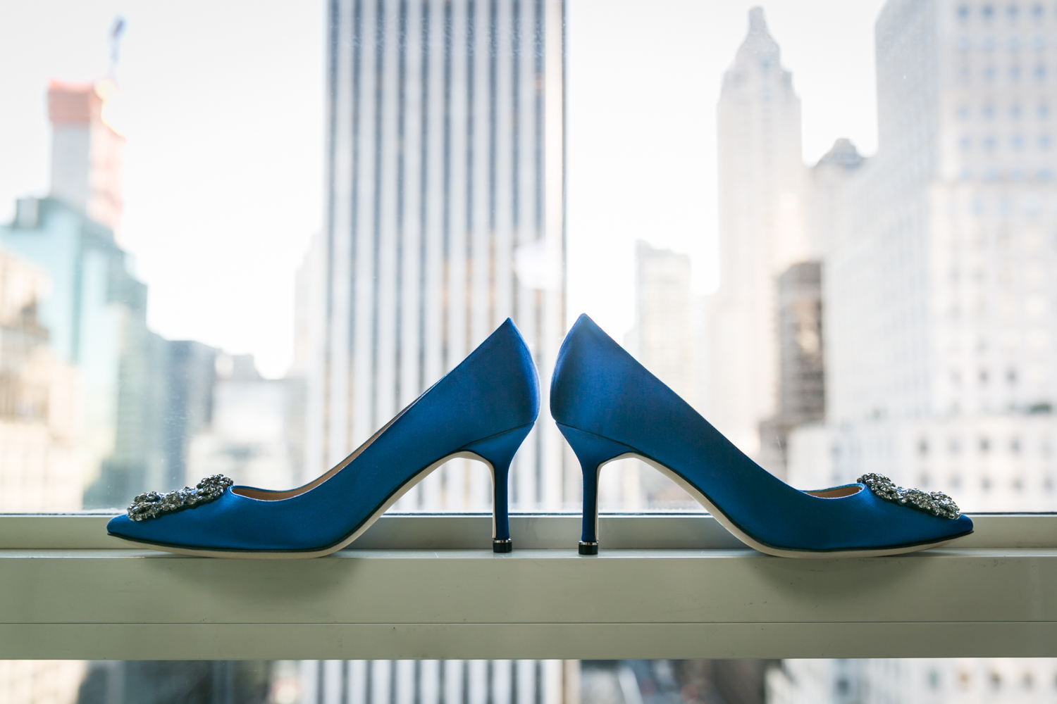 Blue Manolo Blahnik heels in windowsill with NYC skyline in background
