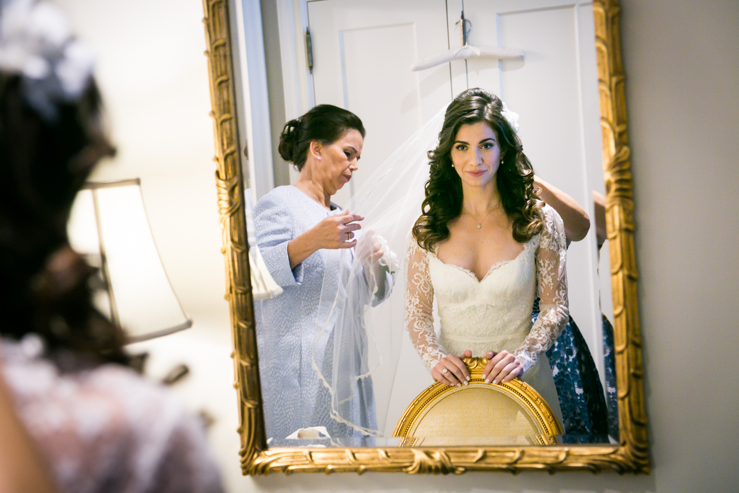 Reflection of bride in mirror putting on veil at a Loeb Boathouse wedding in Central Park