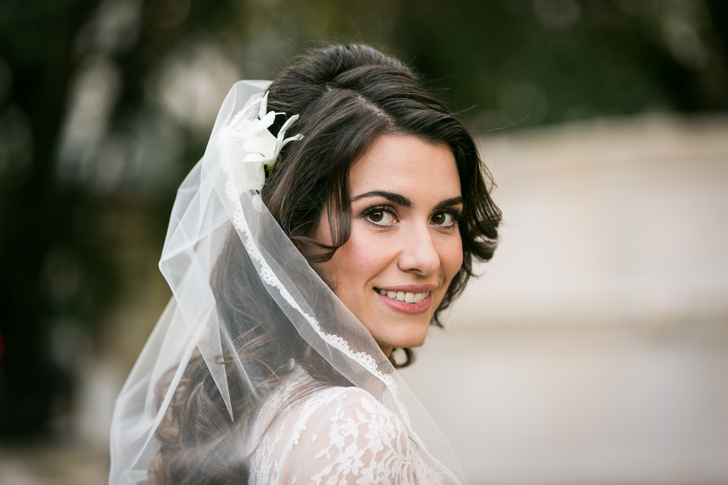 Portrait of bride wearing veil looking over shoulder