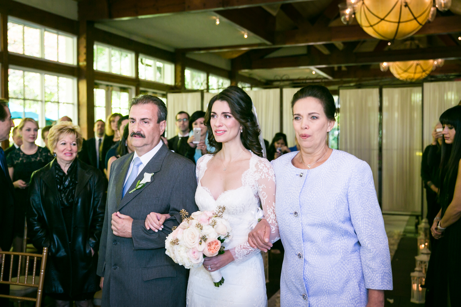 Bride walking down aisle accompanied by both parents at a Loeb Boathouse wedding in Central Park