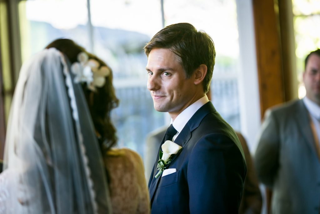 Groom looking over at bride during ceremony at a Loeb Boathouse wedding in Central Park