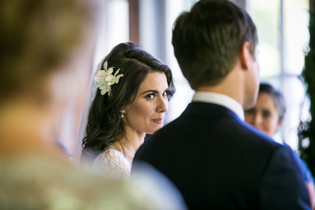 Bride looking over at groom during ceremony at a Loeb Boathouse wedding in Central Park