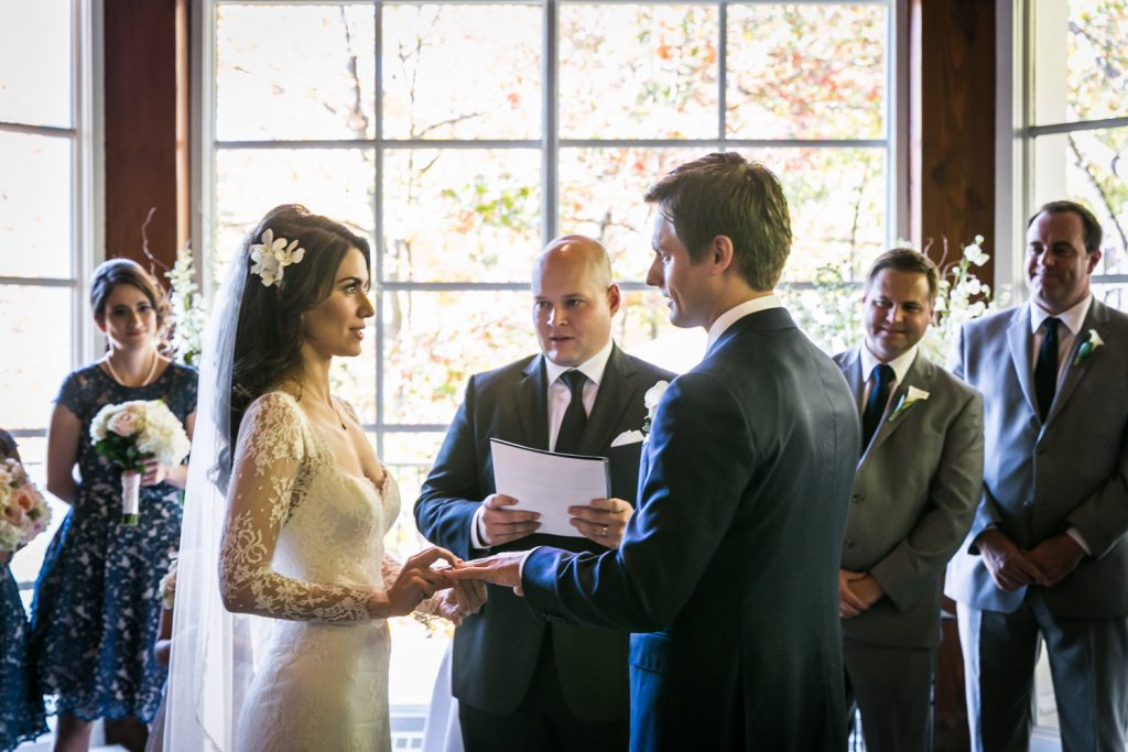 Bride putting ring on groom's finger during Loeb Boathouse wedding ceremony
