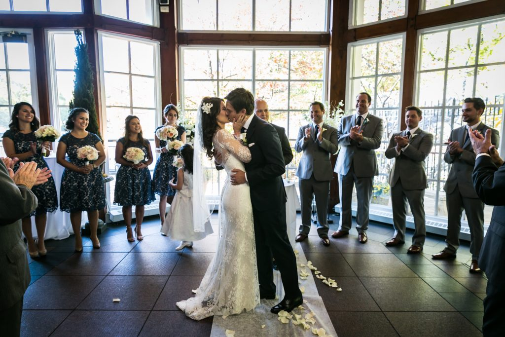 Bride and groom kissing after ceremony at a Loeb Boathouse wedding in Central Park