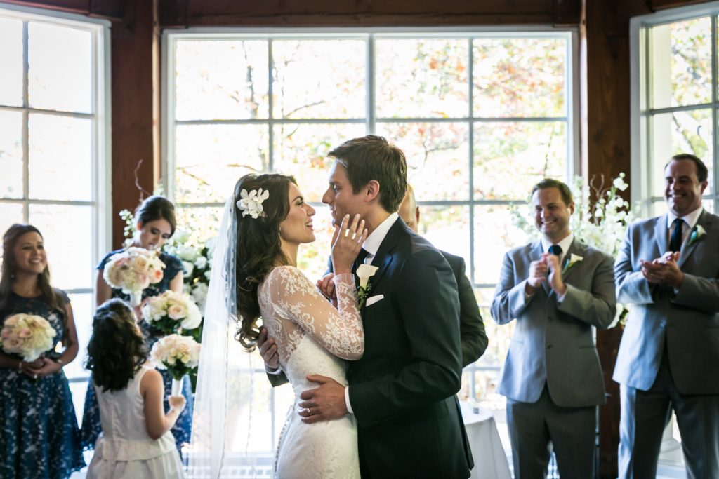 Bride and groom hugging during ceremony at a Loeb Boathouse wedding in Central Park