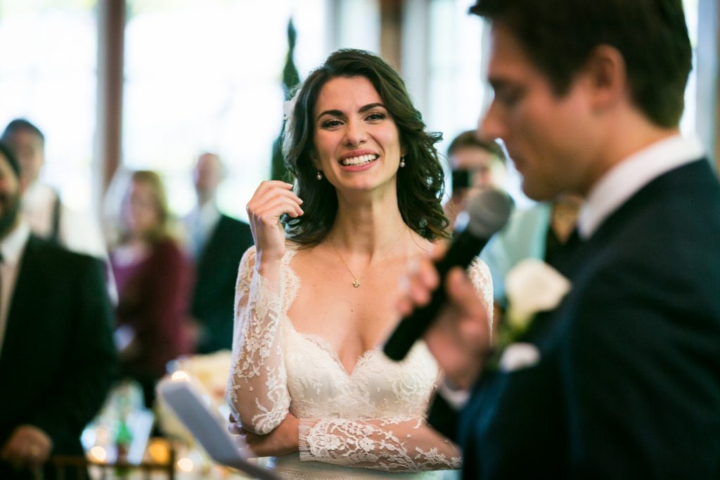 Bride watching groom give speech at a Loeb Boathouse wedding in Central Park