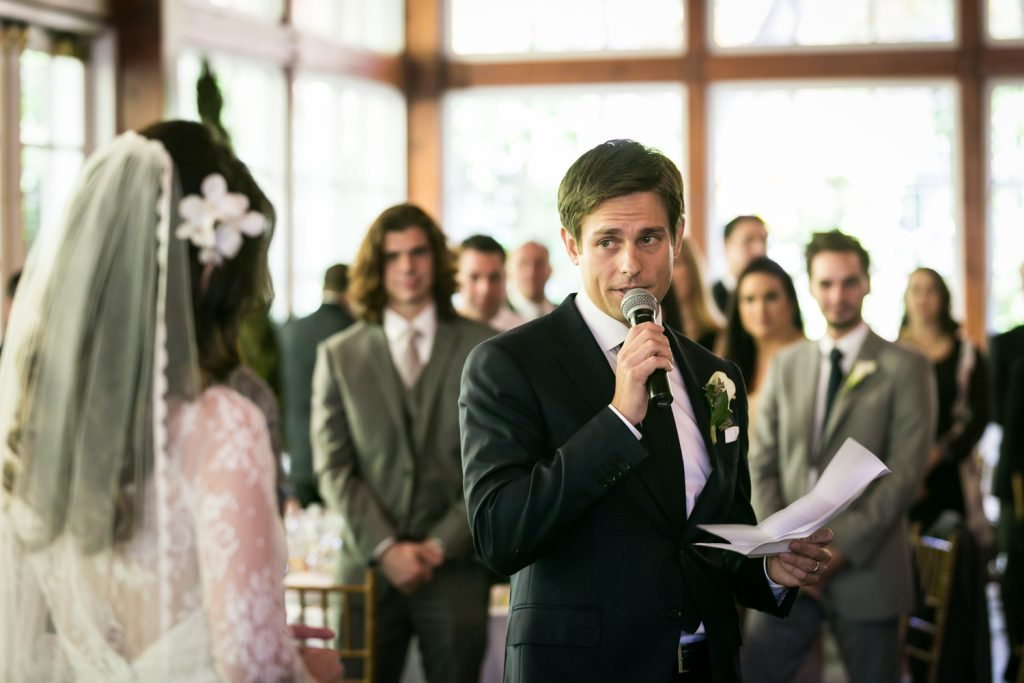 Groom looking at bride while giving speech