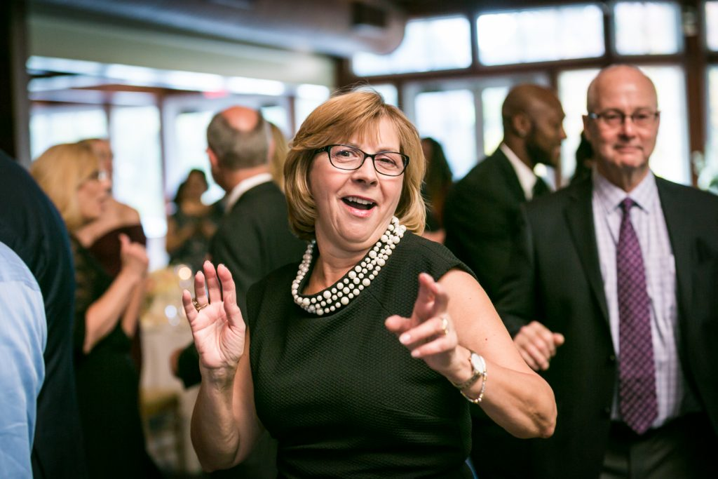 Older woman wearing glasses and dancing at wedding reception