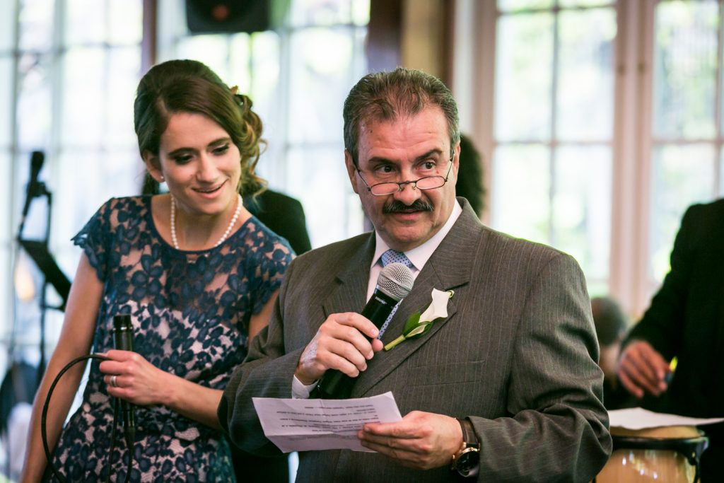 Father of the bride making a speech and maid of honor looking at his paper