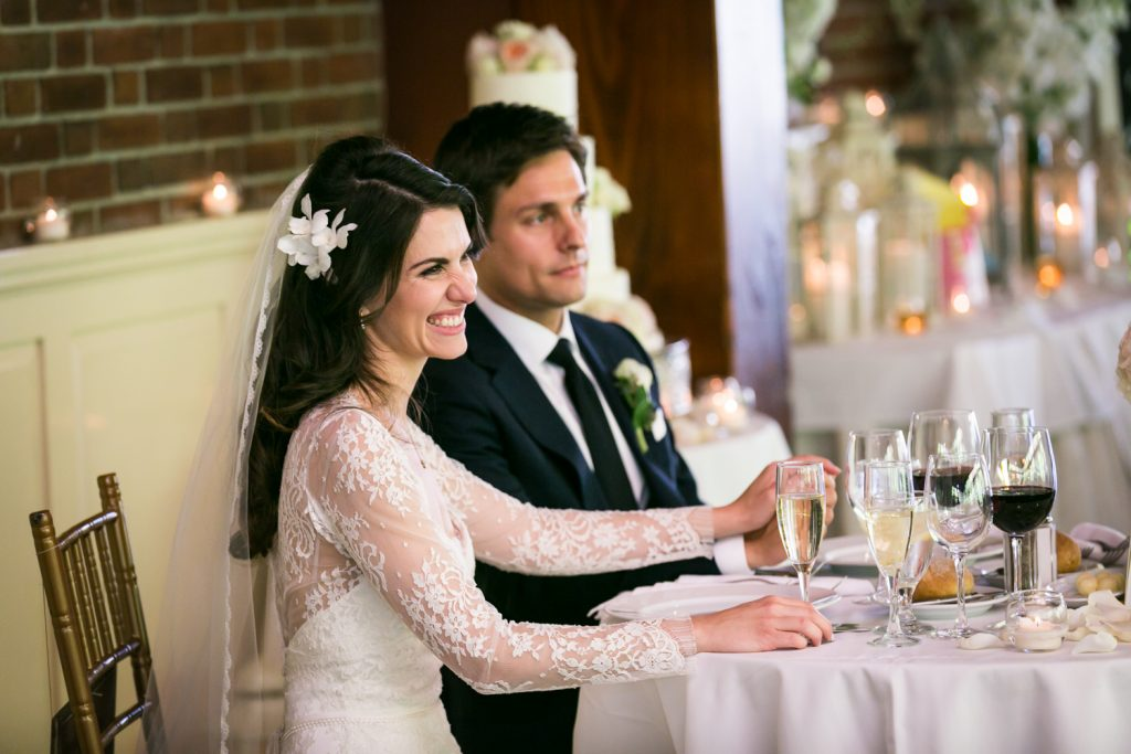 Bride and groom sitting at sweetheart table and listening to toasts