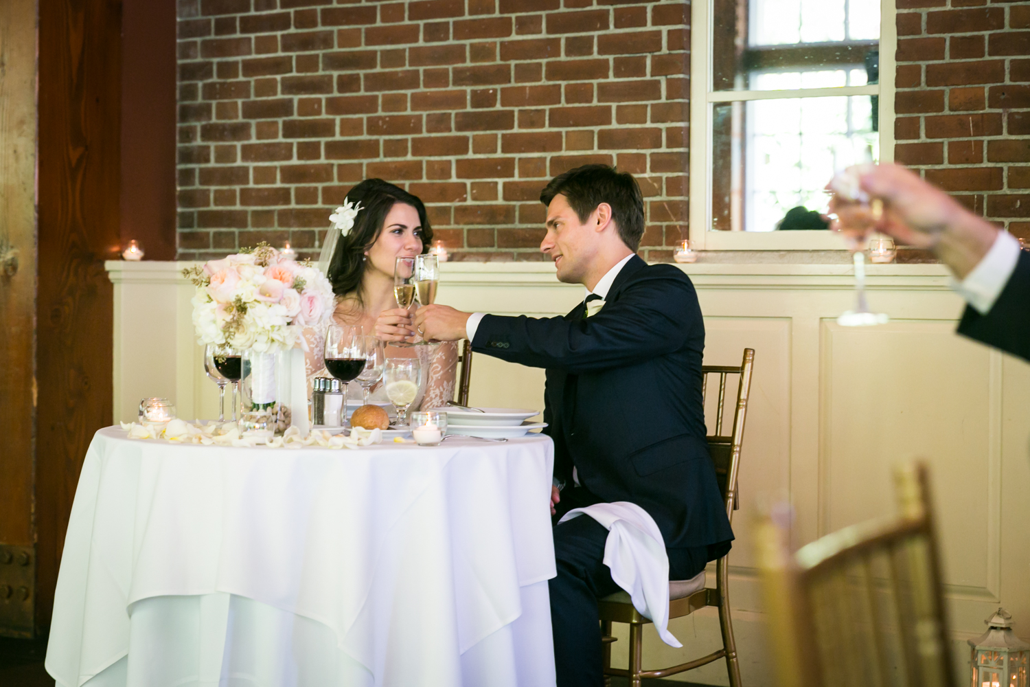 Bride and groom sitting at sweetheart table and toasting champagne glasses