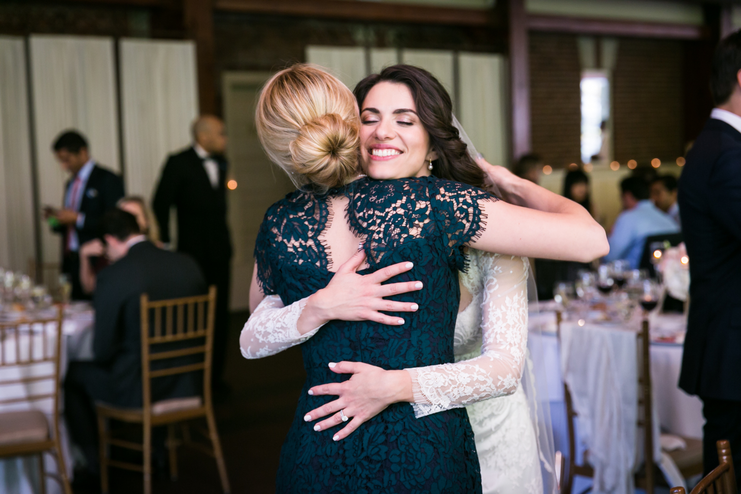 Bride hugging female guest at a Loeb Boathouse wedding in Central Park