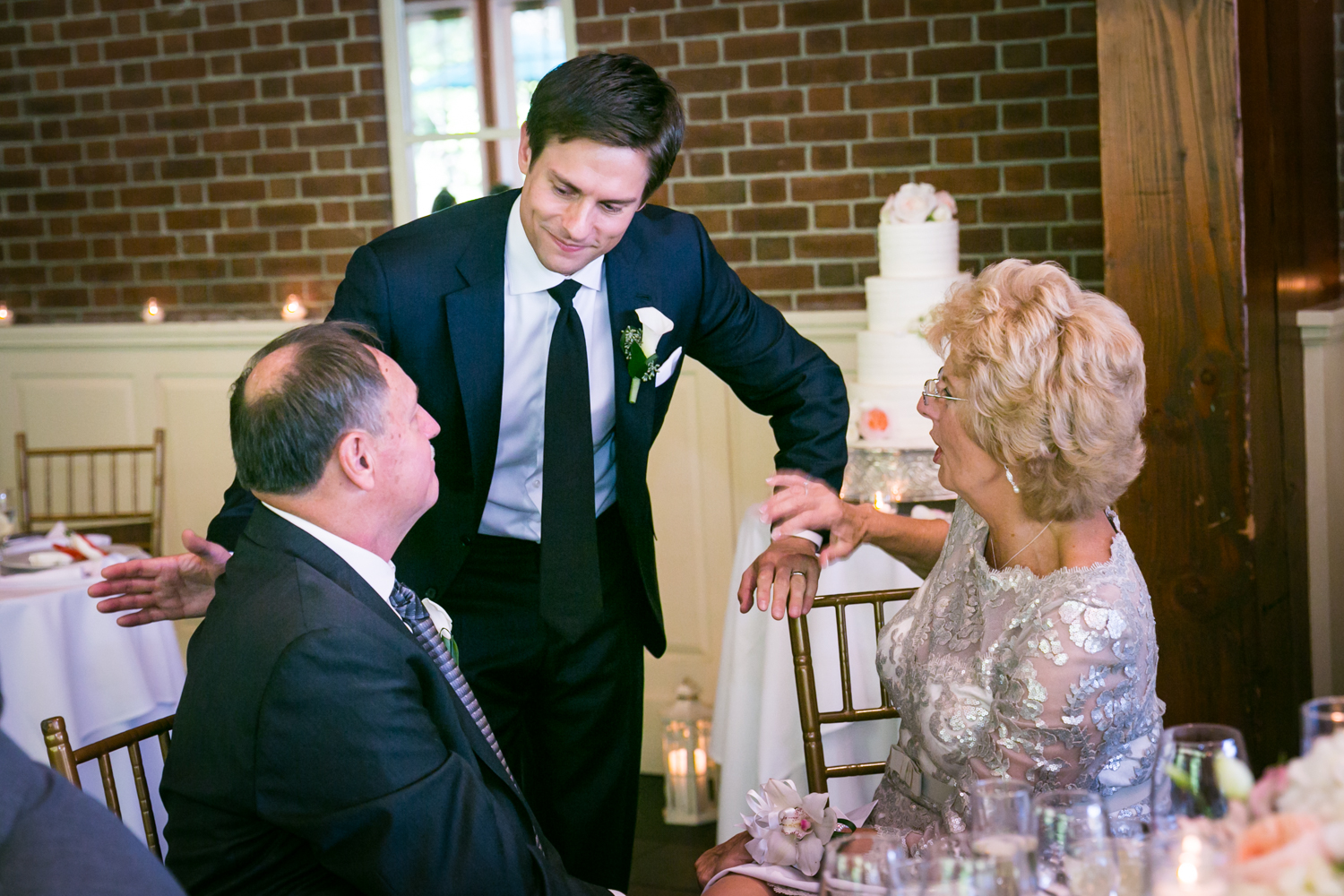 Groom talking with parents seated at table