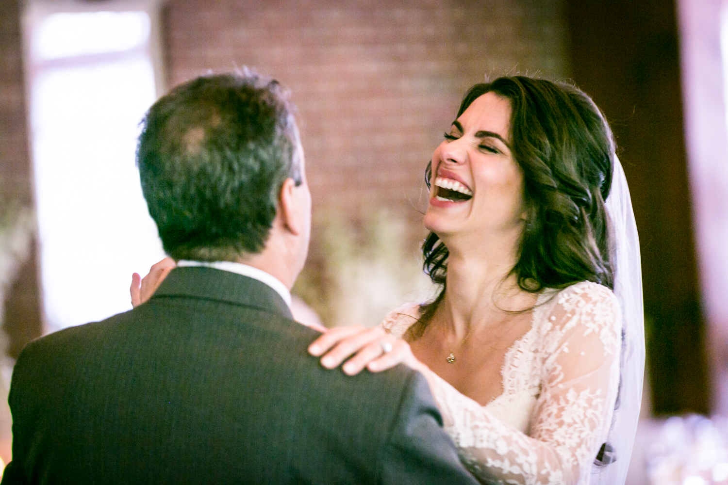 Bride laughing while dancing with father