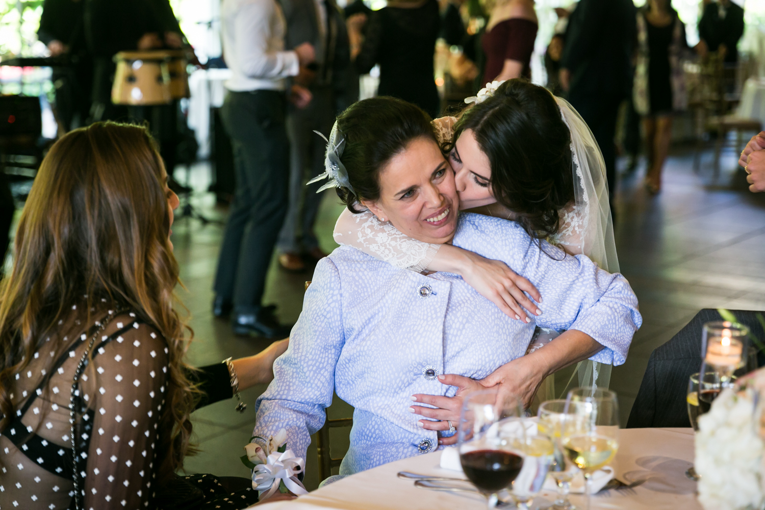 Bride kissing mother seated at table