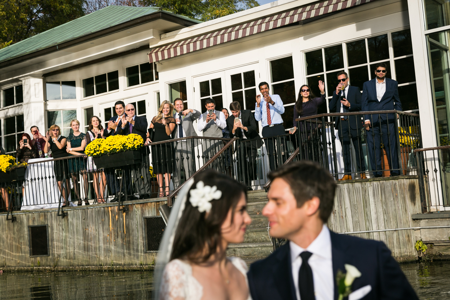 Bride and groom in foreground in boat with guests standing along Loeb Boathouse railing in background