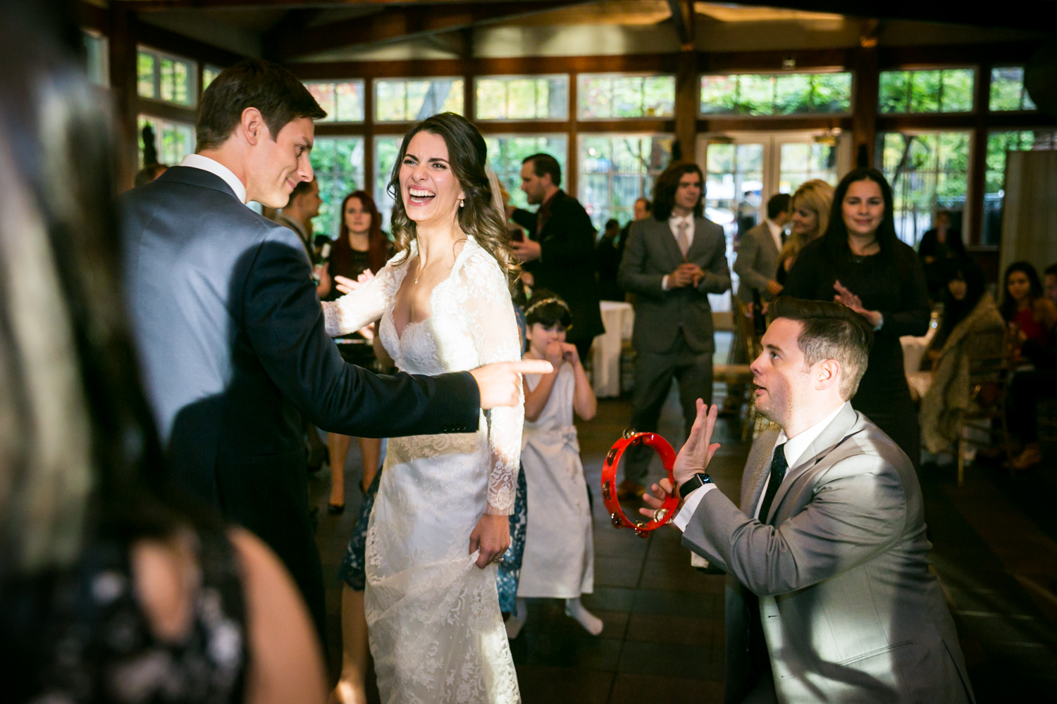 Bride and groom with guest on his knees playing a tambourine