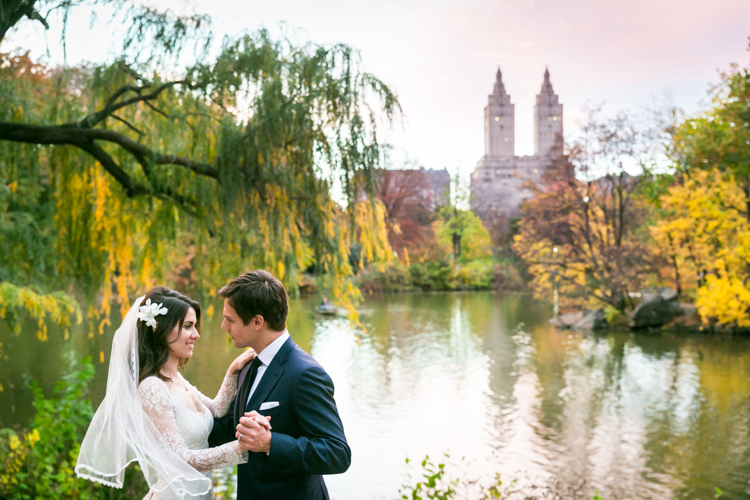 Bride and groom dancing in front of Central Park lake at a Loeb Boathouse wedding
