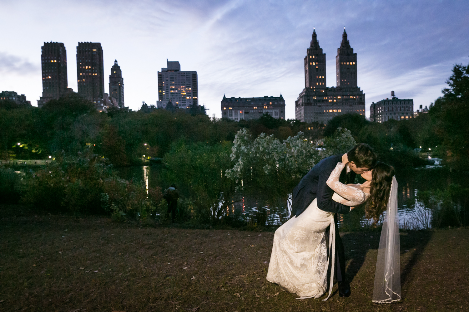 Dramatic kiss in Central Park at night at a Loeb Boathouse wedding