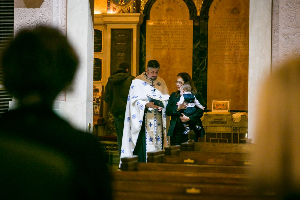 Priest administering rights in cathedral doorway by NYC Greek orthodox baptism photographer, Kelly Williams