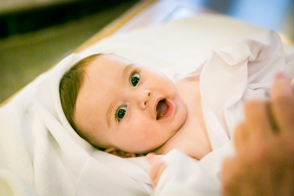 Baby wrapped in towel by NYC Greek orthodox baptism photographer, Kelly Williams